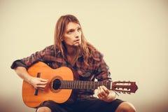 Homme s'asseyant jouant la guitare Photographie stock libre de droits