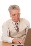 Homme s'asseyant par l'ordinateur portatif Images stock