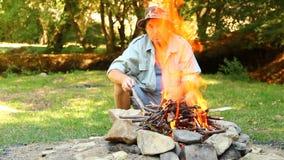 Homme s'asseyant par le feu de camp banque de vidéos