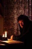 Homme s'asseyant par lueur de chandelle Photos libres de droits