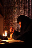 Homme s'asseyant par lueur de chandelle Image stock