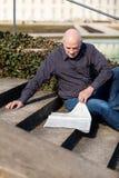 Homme s'asseyant sur des étapes lisant un journal Photographie stock libre de droits
