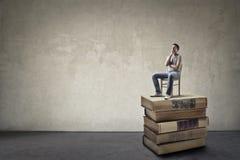 Homme s'asseyant sur des livres Images libres de droits