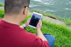 Homme s'asseyant sur l'herbe verte, utilisant le comprimé extérieur photographie stock