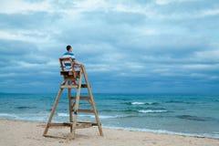 Homme s'asseyant sur la chaise de maître nageur Photos stock