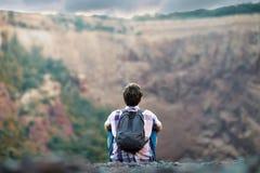 Homme s'asseyant sur la falaise rocheuse photographie stock libre de droits