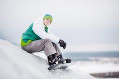 Homme s'asseyant sur la neige avec le surf des neiges Images stock