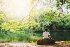 Homme s'asseyant sur la paille sous l'arbre près du canal, image libre de droits