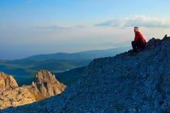 Homme s'asseyant sur la roche Images libres de droits