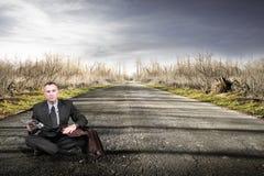 Homme s'asseyant sur la route Image stock