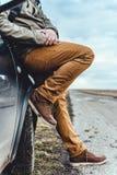 Homme s'asseyant sur la voiture Photographie stock