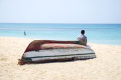Homme s'asseyant sur le bateau. Photo stock