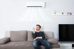 Homme s'asseyant sur le climatiseur fonctionnant de divan photographie stock