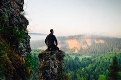Homme s'asseyant sur le dessus de la montagne dans la pose de yoga Photo libre de droits