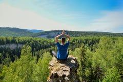 Homme s'asseyant sur le dessus de la montagne dans la pose de yoga Photo stock