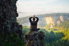 Homme s'asseyant sur le dessus de la montagne dans la pose de yoga Images libres de droits