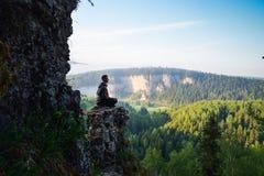 Homme s'asseyant sur le dessus de la montagne dans la pose de yoga, loisirs en harmonie avec la nature Image stock