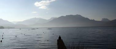 Homme s'asseyant sur le lac Annecy de ponton Photo libre de droits