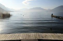 Homme s'asseyant sur le lac Annecy de ponton Photos stock
