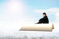 Homme s'asseyant sur le livre volant au-dessus de la ville Photos stock
