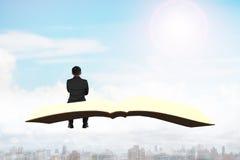 Homme s'asseyant sur le livre volant au-dessus de la ville Image stock