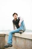 Homme s'asseyant sur le mur Photo stock