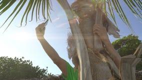 Homme s'asseyant sur le palmier essayant d'obtenir la connexion à son téléphone portable, recherchant la civilisation clips vidéos