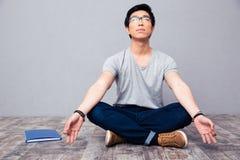 Homme s'asseyant sur le plancher et méditant Photographie stock