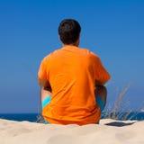 Homme s'asseyant sur le sable Photos libres de droits
