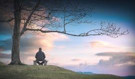 Homme s'asseyant sur un banc en bois r images libres de droits