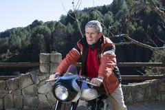 homme s'asseyant sur une moto Photo stock