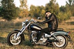 homme s'asseyant sur une moto Images libres de droits