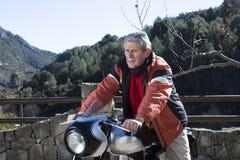 Homme s'asseyant sur une motocyclette Photographie stock