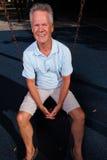 Homme s'asseyant sur une oscillation Image libre de droits