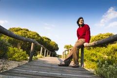 Homme s'asseyant sur une promenade côtière Photo stock