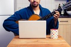 Homme s'enseignant pour jouer la guitare à la maison image stock