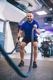 Homme s'exerçant avec des cordes au gymnase image libre de droits