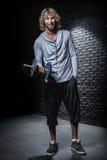 Homme s'exerçant avec des haltères Photographie stock libre de droits