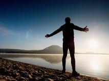 Homme s'exerçant sur la plage Silhouette d'homme actif s'exerçant et s'étendant au lac Photo libre de droits