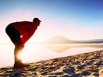 Homme s'exerçant sur la plage Silhouette d'homme actif s'exerçant et s'étendant au lac Photos stock
