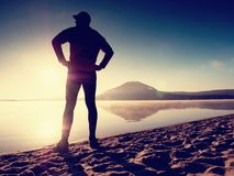Homme s'exerçant sur la plage Silhouette d'homme actif s'exerçant et s'étendant au lac Photographie stock libre de droits