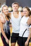 Homme sûr avec les amis féminins se tenant dans le gymnase Photo stock