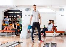 Homme sûr tenant la boule dans le bowling Photos libres de droits