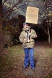 Homme sans abri en parc demandant quelque chose manger Images stock