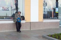 Homme sans abri plus âgé priant pour une certaine somme d'argent près de la boutique de sport sur un bord de mer Image libre de droits