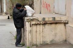 Homme sans abri recherchant la nourriture dans les déchets à Bakou, capitale de l'Azerbaïdjan Image stock