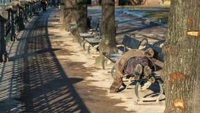 Homme sans abri sur un banc Photos libres de droits