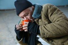 Homme sans abri voracement l'eau potable Photos libres de droits