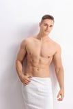 Homme sans chemise bel posant sur un mur blanc Photo stock