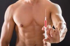 Homme sans chemise de Bodybuilder jugeant la seringue disponible image libre de droits